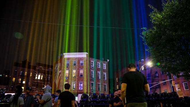 A rainbow light display illuminates the night sky in the West Village near The Stonewall Inn, birthplace of the gay rights movement, Saturday, June 27, 2020, in New York. The light installation was presented by Kind snack foods to mark what would have been the 50th anniversary of the NYC Pride March, which is canceled this year because of the coronavirus pandemic.