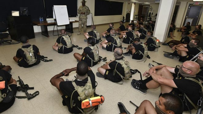 Staff Sgt. James Greening, a drill sergeant assigned to Company A, 3rd Battalion, 10th Infantry Regiment, teaches an anti-terrorism class to trainees in one of the company barracks classrooms. The drill sergeants and trainees wear face coverings and keep to social-distancing protocols under the new controlled monitoring basic combat training model.