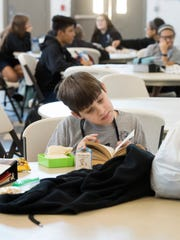 Middle school student Michael Clarke reads a book on