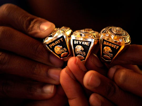 Naples High School football players Greg Pratt, Carlos Hyde and Antwain Harvey hold their rings together after receiving them at a team dinner at Chardonnay Restaurant in Naples on March 24, 2008.