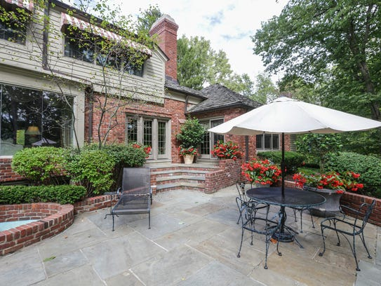 A large stone porch overlooks a man made lake at the