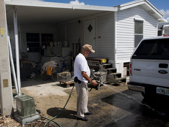 Rod Pascual, 88, washes mud from his driveway in Fisherman's