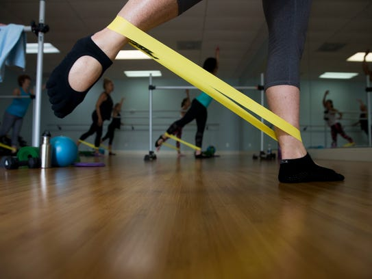 Clients participate in the barre motion class at Beyond