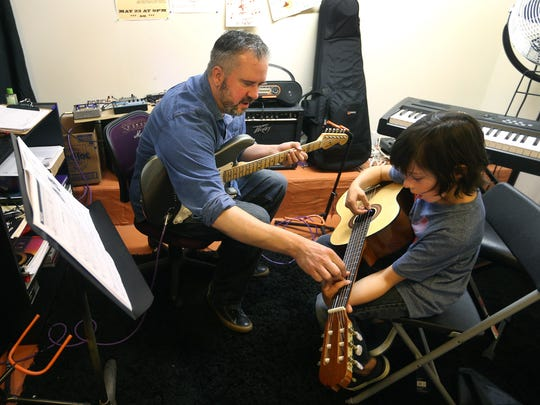 Timm Cash  works on finger positioning with Canyon Shull, 8, during a music lesson at Victor Music Experience.