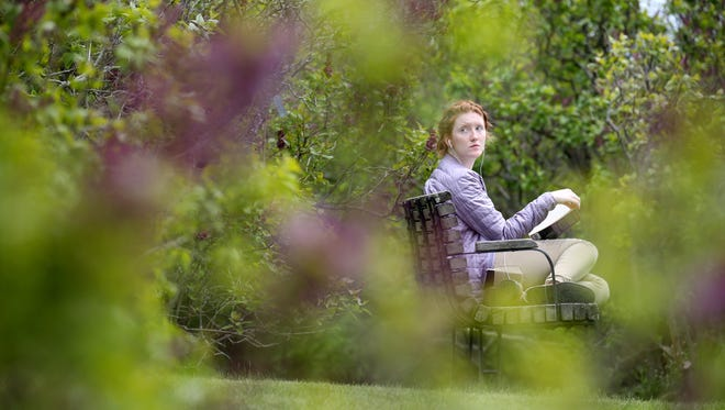 File photo: Mallory Schmackpfeffer enjoys a book among the lilacs during the first day of the Lilac Festival.