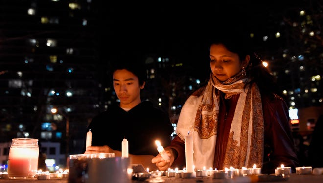 People light candles at a makeshift memorial to the victims after a van mounted a sidewalk crashing into pedestrians in Toronto on Monday, April 23, 2018.