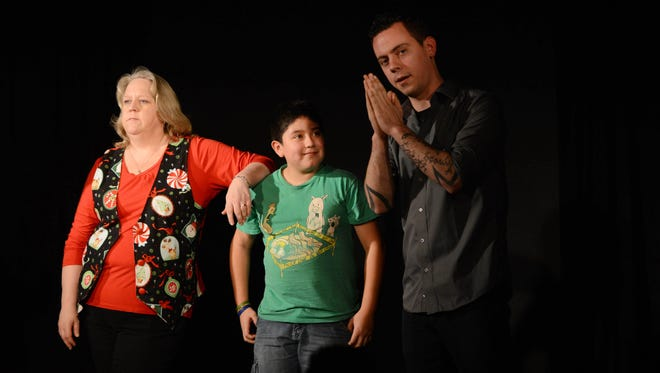 Audience member Jonathan Echavarria participates in an improv session with Julie Harrison and Dave Buerge during a family-friendly show at the Capitol City Theater. The theater will hold an all-ages improv on New Year's Eve.