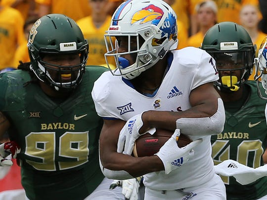 Kansas running back Pooka Williams Jr. (1) is chased down by Baylor Bravvion Roy (99) and Baylor defensive end Deonte Williams (40) during the first half of an NCAA college football game, Saturday, Sept. 22, 2018, in Waco, Texas. (Jerry Larson/Waco Tribune-Herald via AP)