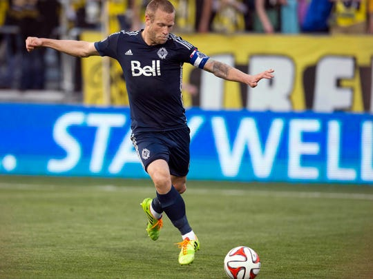 Vancouver Whitecaps defender and former Bay Port standout Jay DeMerit sends the ball upfield against the Columbus Crew in an MLS game. Vancouver won 1-0.