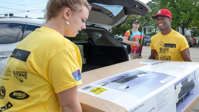 Devontae Gregory, far end, assists in carrying a large box during Sunday's move-in day for UW-Oshkosh students at South Scott Residence Hall on September 4, 2016.