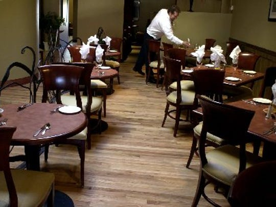 A server sets a table at Jay's Bistro.  -Norm Koch sets a table for dinner at Jay's Bistro Thursday afternoon January 31, 2002 at 135 W. Oak St. Jay's opened Monday January 28 after relocating from their 151 S. College Ave. business.