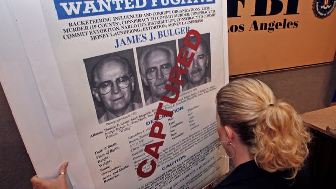 """FBI Special Agent Mary Prang sets up a """"wanted"""" poster overstamped """"captured"""" for James """"Whitey"""" Bulger in Los Angeles on June 23, 2011."""