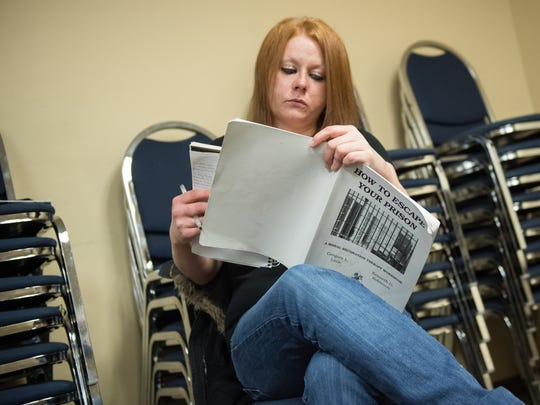 Liz Wratchford reads and writes inside her workbook during class for a 12-step program at the Day Reporting Center on Thursday, Jan. 19, 2017.