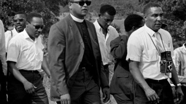 In a June 7, 1966, photograph, Ernest Withers, right, marches with Dr. Martin Luther King, Jr., second from left, in the March Against Fear from Memphis to Jackson, Miss.  At center is Rev. James Lawson.