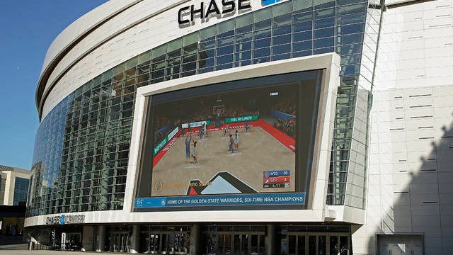 The Chase Center, home of NBA basketball's Golden State Warriors, show a pre-recorded video of a basketball game on a large screen at the entrance to the arena on a day the team was to play the Brooklyn Nets on March 12 in San Francisco. The NBA suspended its season after a Utah Jazz player tested positive Wednesday for the coronavirus.