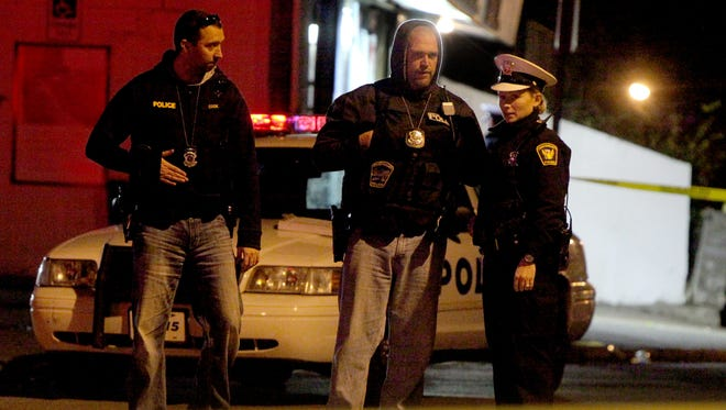 Police investigate after a gun battle in the streets of East Westwood left one dead and three injured Tuesday night.