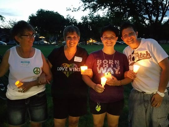 From left, Elise West, Linda Stay, Jade Blanco and Jen Beard clasp arms with other community members, mourning the Orlando shooting victims. The vigil was held Sunday at the Vernon Worthen Park.