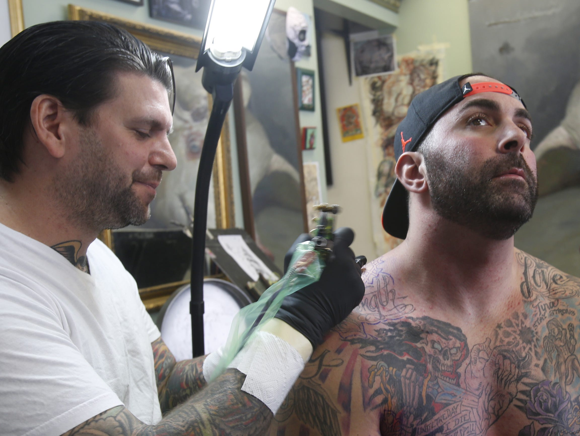 J.R. Maloney, owner of Vanguard Tattoo of Nyack, works on a memorial sleeve for Michael Sayegh of Thiells. The sleeve is principally in honor or Sayegh?s sister who died of cancer as well as other family members. J.R. Maloney, owner of Vanguard Tattoo of Nyack, works on a memorial sleeve for Michael Sayegh of Thiells on Oct. 30, 2014. The sleeve is principally in honor or Sayegh's sister who died of cancer as well as other family members.