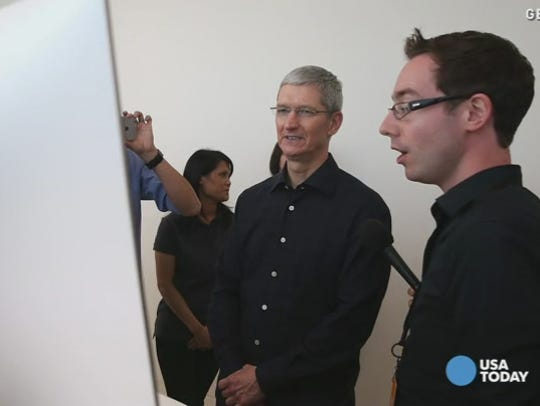 Apple CEO Tim Cook looks at the new iMac.