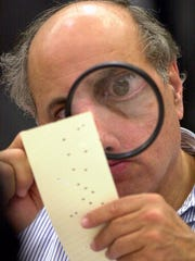FILE - In this Nov. 24, 2000 file photo, Broward County, Fla. canvassing board member Judge Robert Rosenberg uses a magnifying glass to examine a disputed ballot at the Broward County Courthouse in Fort Lauderdale, Fla. What happens if America wakes up on Nov. 9 to a disputed presidential election in which the outcome turns on the results of a razor-thin margin in one or two states, one candidate seeks a recount and the other goes to court?  (AP Photo/Alan Diaz, File)