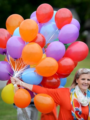 Although a staple of celebration, balloons can be harmful to the environment. Here, a Tennessee principal gets ready to pass out balloons to release in a ceremony to say goodbye to mark the transition for students and teachers from one school to another.