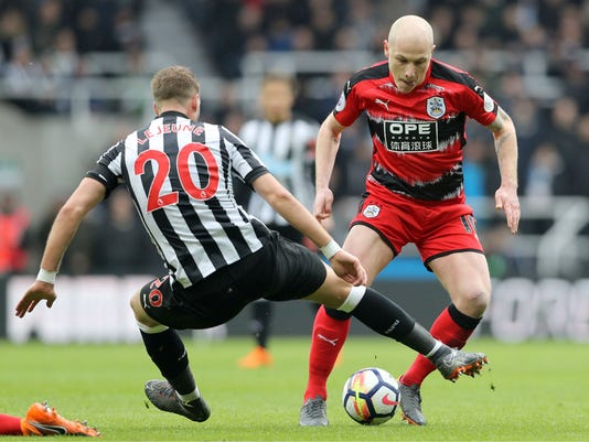 Newcastle United's Florian Lejeune, left, and Huddersfield Town's Aaron Mooy battle for the ball during their English Premier League soccer match at St James' Park, Newcastle, England, Saturday, March 31, 2018. (Owen Humphreys/PA via AP)