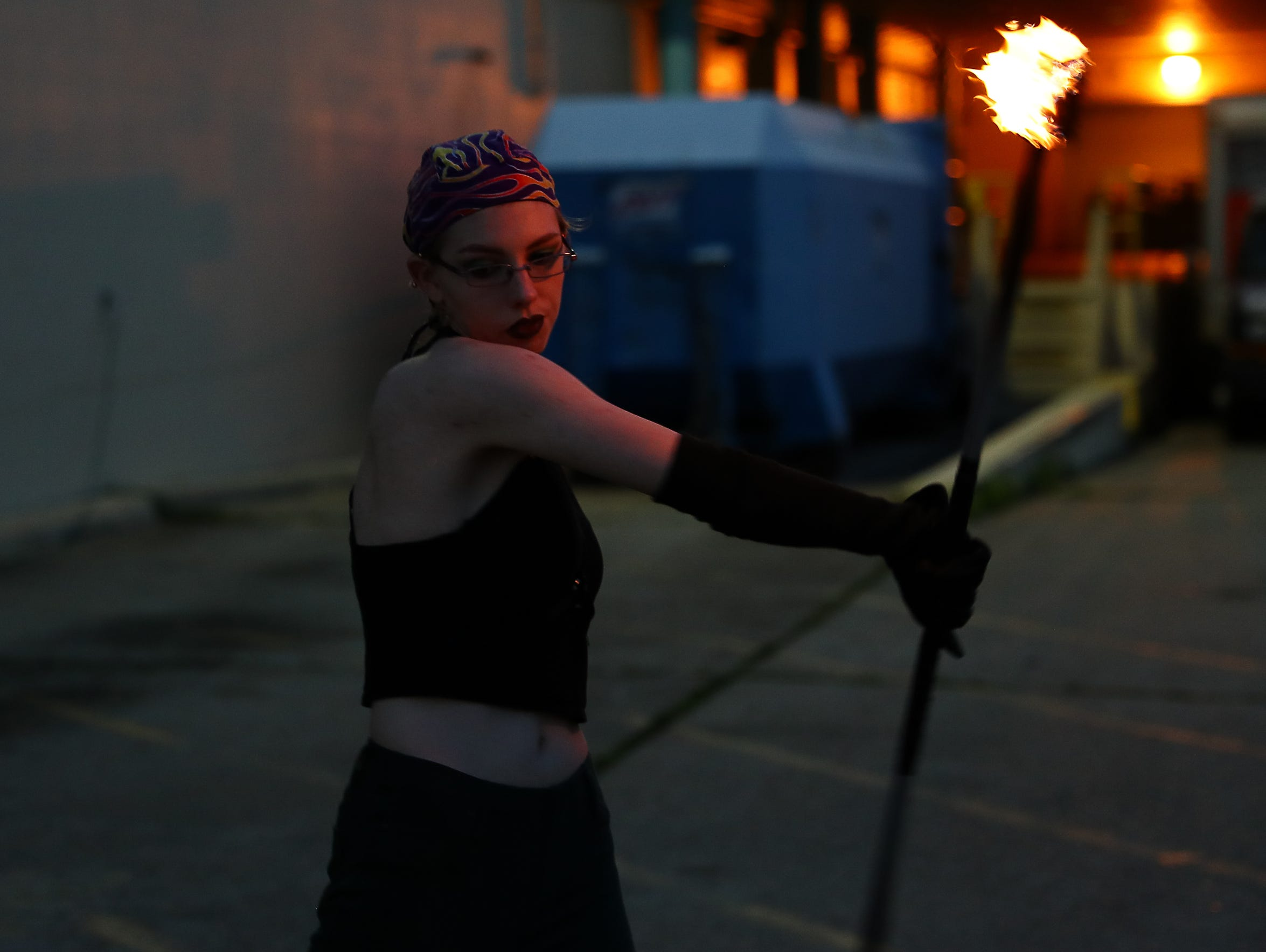 Viktoria Birr demonstrates fire spinning outside the