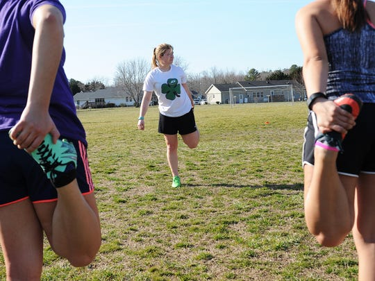 Ryan Wright leads her teammates in warmup drills and stretching at girls soccer practice at Nandua High School on Tuesday, March 8, 2016. Wright, a senior on the Warriors' soccer team, recently signed to play women's soccer at Salisbury University.