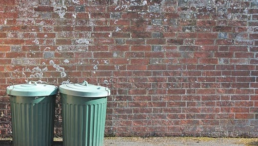 dustbins outside against brick wall