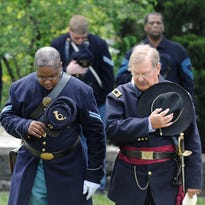 Fort Negley reenactor Color Guard members Gary Burke, left, and Dave DuBrucq bow their heads during a prayer for military veterans during a Memorial Day observance ceremony held at Fort Negley on Saturday.