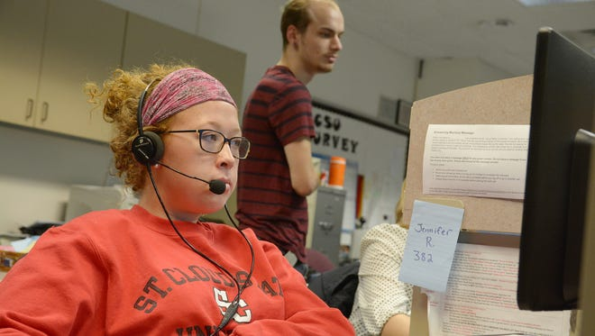 Student Jennifer Rasmussen of Sauk Rapids works on her computer as student director Mike Grewatz of Duluth supervises during the fall 2015 SCSU Survey.