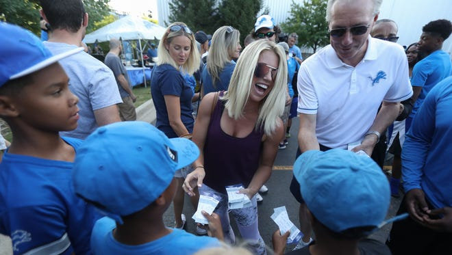 Kelly Stafford, wife of Lions quarterback Matthew Stafford, and Lions president Rod Wood hand out tickets to a preseason game Wednesday at the practice facility in Allen Park.