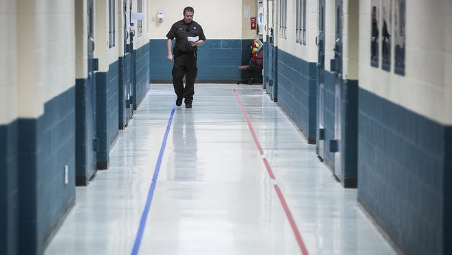An officer patrols a hallway in the Delaware County Jail.