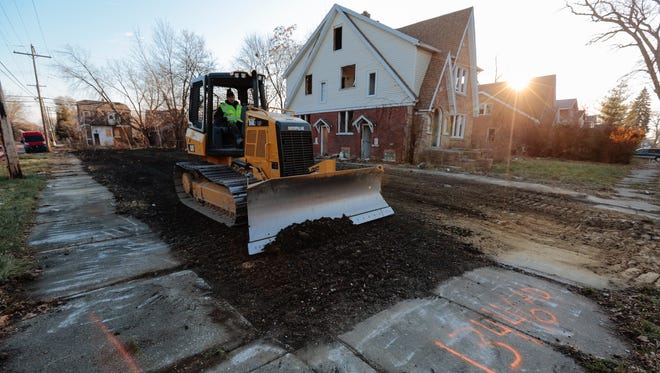 Workers from Adamo Demolition work on the final grading of a lot where a house was demolished on Elmdale Street on Detroit's east side on Thursday, Dec. 4, 2014. Shortages of clean dirt to fill in basements and lots have challenged the cleanup effort.