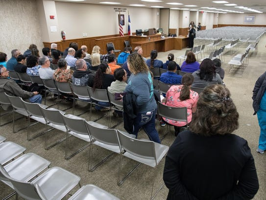 People are seated for jury duty inside the Central
