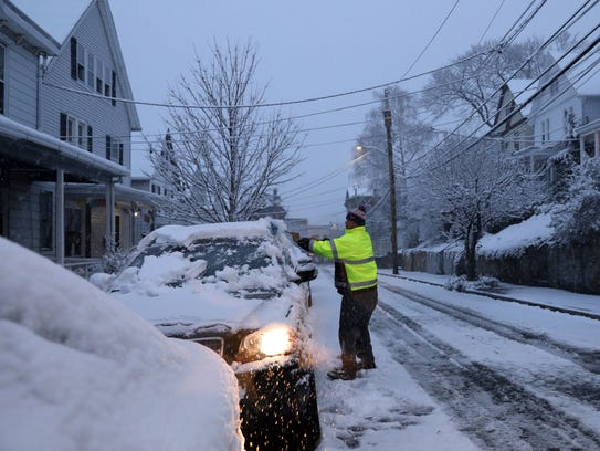 A man clears snow off his car in Tarrytown on April