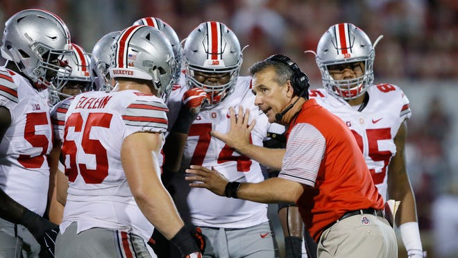 FILE - In this Sept. 17, 2016, file photo, Ohio State head coach Urban Meyer talks with his players in the fourth quarter of an NCAA college football game against Oklahoma, in Norman, Okla. Meyer's current suspension and previous paid leave have restricted him from talking football with his staff and athletes during August with one exception _ a team meeting the day after the suspension was announced. Emails from the senior vice president for human resources show Meyer and athletic director Gene Smith were allowed to meet with the players and coaches last Thursday, Aug. 23, 2018. (AP Photo/Sue Ogrocki, File)