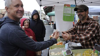 Randall Veenstra takes a taste of garlic mushrooms from Dan Lipow  at the Ramsey Farmer's Market Garlic Fest.
