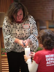 Oradell Mayor Dianne Didio lights a candle after sharing