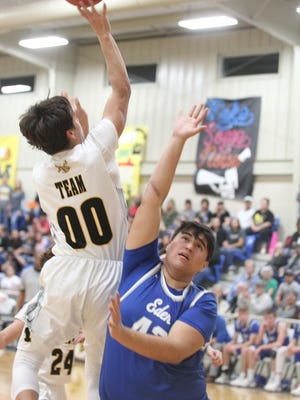 Menard High School's Christian Salazar (00) Chputs up a shot as Eden's Nate Hernandez defends on the play during a District 16-1A basketball game at the Menard gym on Friday, Feb. 9, 2018.