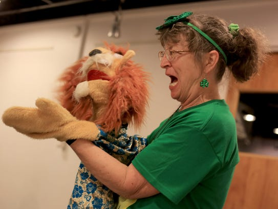 Lorie Hawley performs on March 17 with a puppet during