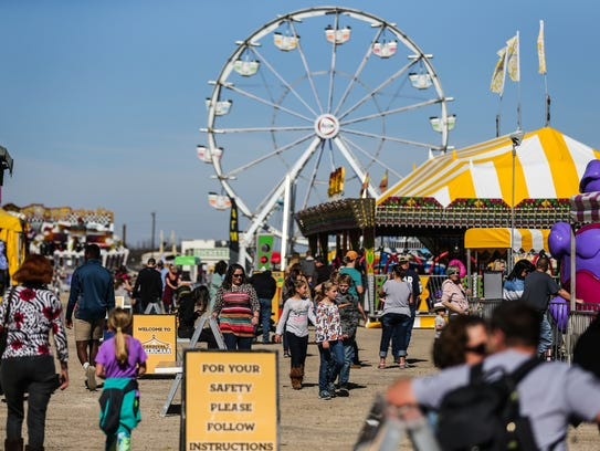 Visitors stroll in the midway during the San Angelo