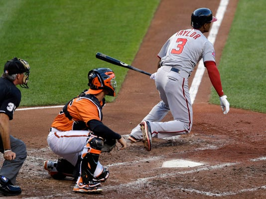 Washington Nationals' Michael Taylor (3) watches his single in front of Baltimore Orioles catcher Caleb Joseph, center, and home plate umpire Paul Nauert, left, in the second inning of an interleague baseball game, Saturday, July 11, 2015, in Baltimore. Nationals' Danny Espinosa scored on the play. (AP Photo/Patrick Semansky)