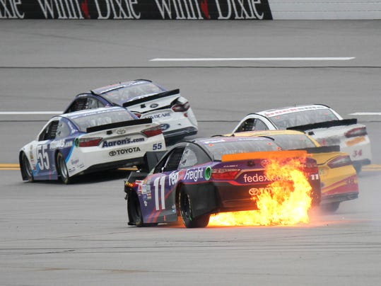 Sprint Cup Series driver Denny Hamlin (11) brings his burning car to a stop after being involved in a crash during the NASCAR Sprint Cup Series auto race at Talladega Superspeedway Sunday, Oct. 25, 2015, in Talladega, Ala. (AP Photo/Russell Norris)