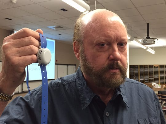 Project Lifesaver International instructor Gary Reynolds shows a wristband transmitter used in the program to track wandering people, part of training New Castle County police officers Wednesday as program trainers.