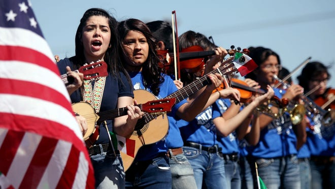 FILE--In this May 3, 2014, file p goto, members of the Ector Junior High Mariachi Band perform while riding on a float during the Cinco de Mayo parade on Crane Avenue in Odessa, Texas. Trump's immigration policies and rhetoric are leaving some Mexican Americans and immigrants feeling at odds with a day they already thought was appropriated by beer and liquor companies, event promoters and local bars. (Edyta Blaszczyk/Odessa American via AP, file)