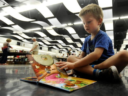 Andrew Gray, 4, reads one of his books while waiting for his mother to finish looking through books during the Friends of the Library book sale on Friday, June 16, 2017, at the Abilene Convention Center.