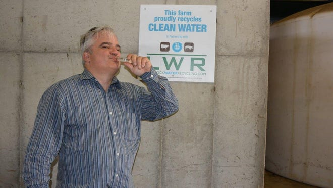 Ross Thurman, president of Livestock Water Recycling, drinks the potable water that was created with his company's manure treatment system.