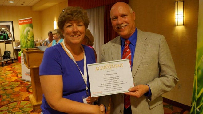 """Susan Engelsman, left, accepts a certificate for successfully completing the """"Green Boot Camp."""""""