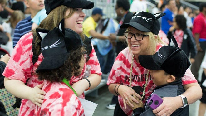 Pleasant Run Panther Bot robotics team coach Nicole Oliver, from left, hugs Jose Verastegui, 10, as coach Lisa Hopper hugs Angel Herrera, 10, following a successful contest event at the VEX worlds robotics competition at the Kentucky Exposition Center in Louisville on Monday.
